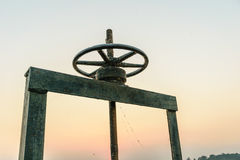 Wheel for drain water. Old black wheel for drain water or floodgate , evening sky background stock photo