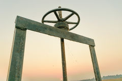 Wheel for drain water. Old black wheel for drain water or floodgate , evening sky background stock photos