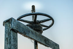 Wheel for drain water. Old black wheel for drain water or floodgate , evening sky background stock image