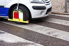 Wheel drive blocker. Vehicle wrongly parked over the pedestrian crossings with fixed wheel drive blocker Stock Photography