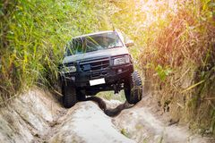 4 wheel drive in the forest. 4 wheel drive is climbing on a difficult off-road in mountain forests in Thailand Royalty Free Stock Images