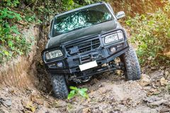 4 wheel drive in the forest. Chon Buri, Thailand-Dec 5, 2017: A 4 wheel drive is climbing on a difficult off-road in mountain forests in Thailand Royalty Free Stock Photo