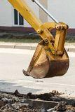 Wheel excavator digging trench on rocky land Stock Photo