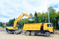 The wheel excavator loads the earth with a bucket to the body of a multi-ton dump truck on the construction site.  royalty free stock photography
