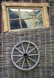 Wheel. fence. window. Rural still life piece. Wicker fence vine with a wooden wheel wagon stock image