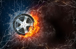 Wheel in fire and water. Wheel on fire and water with lightening around on black background. Horizontal layout with text space Royalty Free Stock Photo