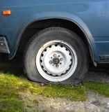 Wheel with a flat tire. Dusty rusty wheel with a flat tire of the old car standing on a roadside royalty free stock photography