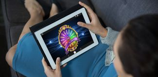 Composite image of wheel of fortune on mobile screen. Wheel of fortune on mobile screen against female business executive using digital tablet Stock Photo