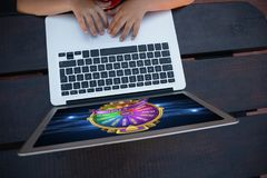 Composite image of wheel of fortune on mobile screen. Wheel of fortune on mobile screen against overhead view of boy using digital laptop while sitting at table Royalty Free Stock Photography