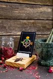 The Wheel of Fortune from the Tarot Major Arcana on a card stand. With pink dried rose buds and green marble mortar and pestle on gray slate background stock image