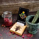 The Wheel of Fortune from the Tarot Major Arcana on a card stand. With pink dried rose buds and green marble mortar and pestle on gray slate background royalty free stock photo
