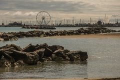 A wheel on the horizon. The port of rimini hosts a large 60 meter high ferris whell place of origin rotterdam Royalty Free Stock Images