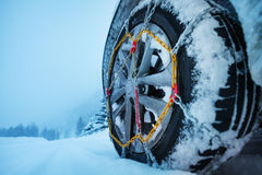 Wheel with ice chains for tire on a snowy road Royalty Free Stock Image