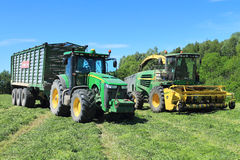 The wheel John Deere 8335R tractor with the trailer and the fodder harvesting John Deere 7450 combine. In the field royalty free stock images