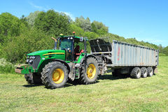 The wheel John Deere 7930 tractor with the trailer with a mowed grass Royalty Free Stock Photos