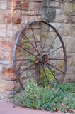 Wheel leaning against brick stone wall Stock Image