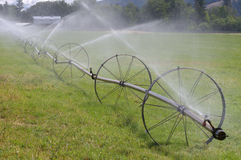 Wheel Line Irrigation System. A hay pasture near Vernon, British Columbia is irrigated with a Wheel Line Irrigation system.  A water motor propels the sprinklers Stock Image