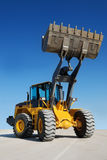 Wheel loader. With fully raised bucket (in focus) over blue sky Royalty Free Stock Images