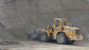 Wheel loader bulldozer unloading sand in sandpit stock footage
