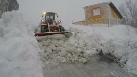 Wheel loader clearing snow from driveways, winter road maintenance. PETROPAVLOVSK CITY, KAMCHATKA PENINSULA, RUSSIA - DEC 29, 2017: Front End Wheel Loader stock video footage