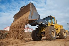 Wheel loader at eathmoving works. Wheel loader machine unloading sand at eathmoving works in construction site Stock Photos
