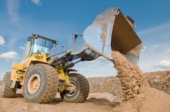Wheel loader excavation working. Wheel loader machine unloading sand at eathmoving works in construction site Royalty Free Stock Photo