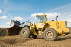 Wheel loader excavation working. Wheel loader machine unloading sand at eathmoving works in construction site Stock Photography