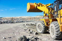 Wheel loader excavator at granite or iron ore opencast mine Royalty Free Stock Images
