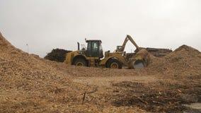 Wheel loader excavator shoveling up wood chips. Shot of Wheel loader excavator shoveling up wood chips stock video footage