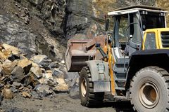A wheel loader / front loader machine working on a heap of stones with its shovel at a quarry. Those machines can be used in mining and construction industry as Stock Photo