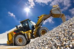 Wheel loader in a gravel pit during mining - heavy construction. Machine in open cast mining royalty free stock photography