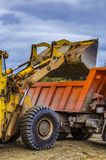 Wheel loader loading ore into dump truck at opencast. rain clouds royalty free stock photography