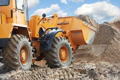 Wheel loader machine. Unloading sand at eathmoving works in construction site Royalty Free Stock Photography