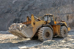 Wheel loader machine. Unloading rocks in the open-mine of iron ore Royalty Free Stock Photos
