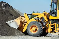 Wheel loader machine. Unloading sand at eathmoving works in construction site Stock Photos