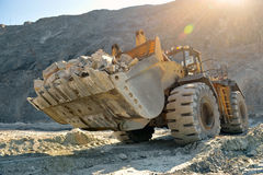 Wheel loader machine. Unloading rocks in the open-mine of iron ore Royalty Free Stock Images