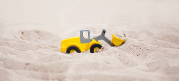 Wheel Loader. Model. Model wheel loader in the sand. Yellow wheel loader works in the sand Stock Images