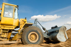 Wheel loader over blue sky. Wheel loader machine loading sand at eathmoving works in construction site over blue sky Stock Photography