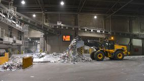 Wheel loader transports waste paper for recycling in a mill - pa. Per production in a mill stock image