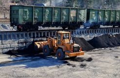 Wheel loader unload coal at railway station in a mining quarry. Wheel loader unload coal at a cargo railway station in a mining quarry royalty free stock images