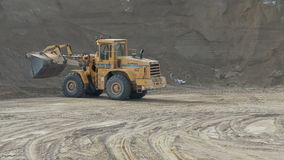 Wheel loader unloading sand at earthmoving works. In construction site stock video