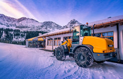 Wheel loader winter adapted. A yellow wheel loader with chains on its tires, ready to remove the snow from the mountain paths. A lovely winter scenery from the Stock Images