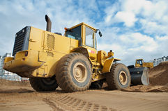 Wheel loader at work. Wheel loader machine loading sand at eathmoving works in construction site Stock Photography