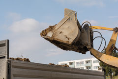 Wheel loaders tilts earth in truck. Dump truck shoveling earth from construction loaders - Closeup Stock Photos