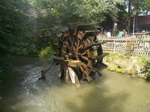 The wheel of the mill. An old wooden wheel in the middle of the river Stock Image