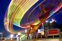 Wheel in motion. Having fun in Ferris wheel illuminated at night in amusement park Stock Image