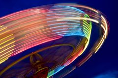 Wheel in motion. Having fun in Ferris wheel illuminated at night in amusement park Stock Images