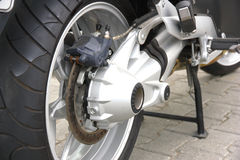 Wheel of motorcycle. Black wheel of a motorcycle with the chromeplated muffler the rear view Stock Photography
