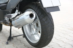 Wheel of motorcycle. Black wheel of a motorcycle with the chromeplated muffler the rear view Royalty Free Stock Photo