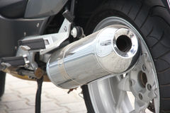 Wheel of motorcycle. Black wheel of a motorcycle with the chromeplated muffler the rear view Royalty Free Stock Image